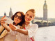 Outdoor portrait of two happy women taking a self picture using a smart phone with Houses of Parliament and Big Ben in the background.
